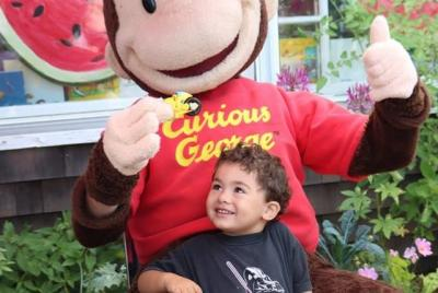 Curious George with one of his young fans